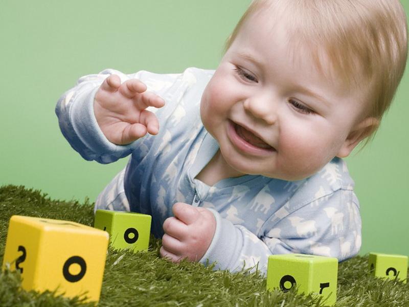Малыш тянется к кубику